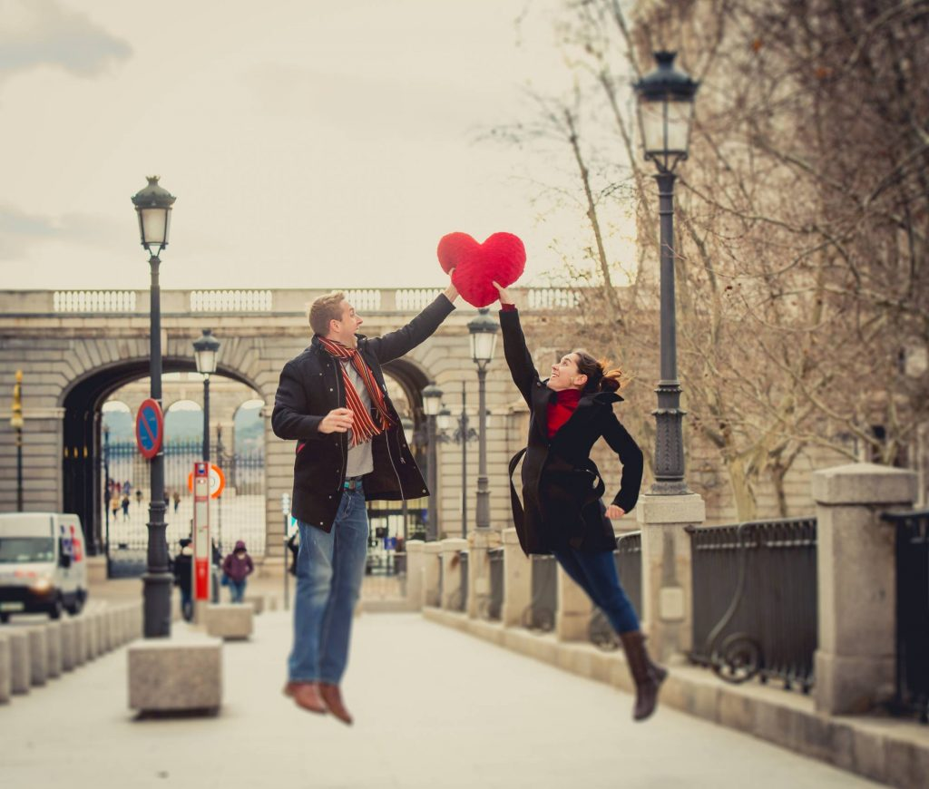 couple playing with a heart shaped cushion in winter